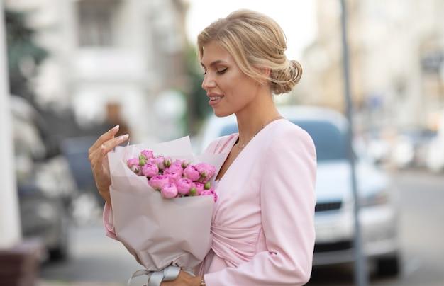 Женщина, держащая розовые цветы на открытом воздухе
