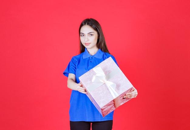 Donna che tiene una scatola regalo rosa legata con un nastro bianco.