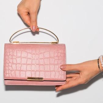 ピンクの革のハンドバッグを持っている女性