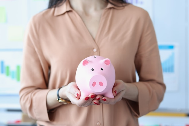 Woman holding pink piggy bank in office closeup