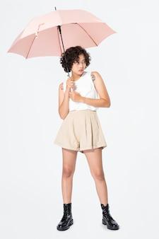 ピンクの傘のカジュアルな服装を保持している女性