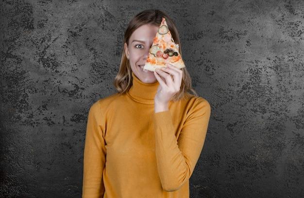 살라미 소시지와 피자를 들고 웃고, 얼굴의 일부를 덮는 여자