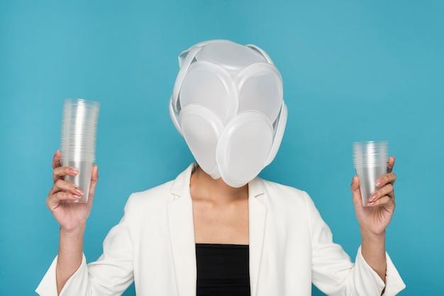 Donna che mantiene i bicchieri di plastica