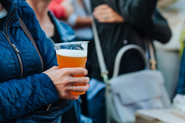 Woman holding plastic glass with beer at festival