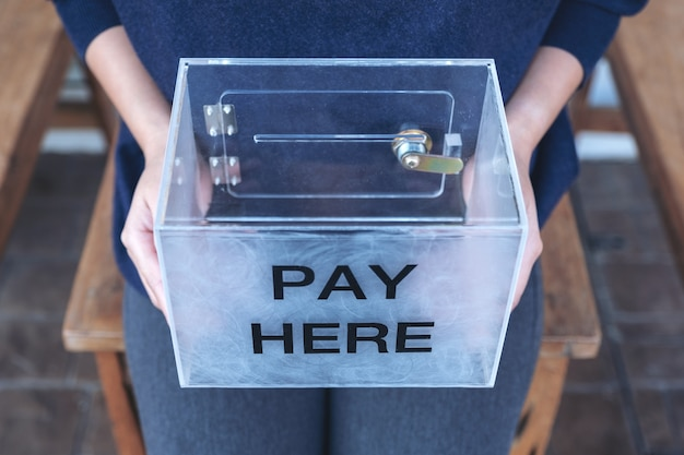 A woman holding a plastic payment box