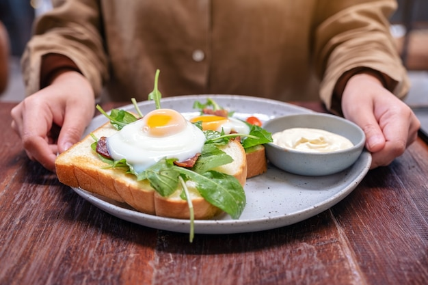 A woman holding a plate of breakfast sandwich with eggs, bacon and sour cream on wooden table