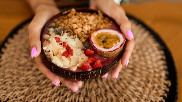 Woman holding plate coconut plate with tasty smoothie bowl.