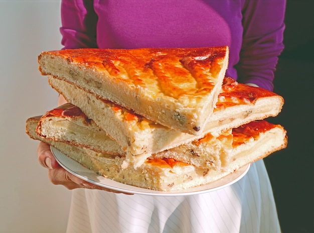 Woman holding a plate of sliced armenian traditional breads stack called gata