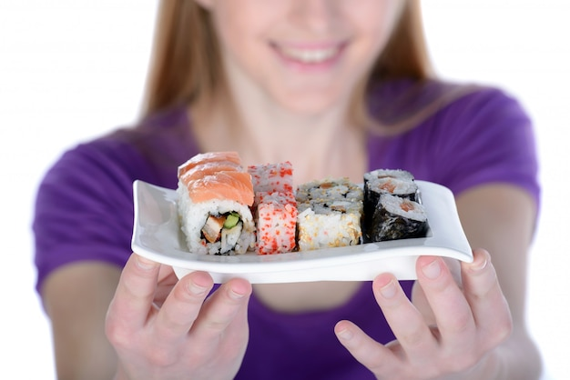 Woman holding a plate of sushi while standing on white.