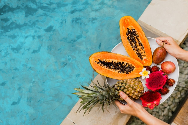 Woman holding plate of tasty tropical exotic fruits on the edge of pool, breakfast at luxury hotel.