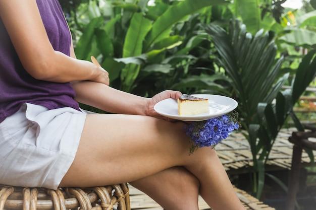 庭に座っているチーズケーキのスライスとプレートを保持している女性。