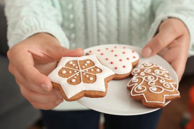 おいしいジンジャーブレッドクッキーとプレートを保持している女性、クローズアップビュー