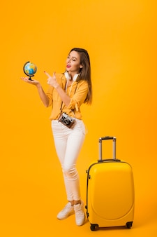 Woman holding and pointing at globe with luggage next to her