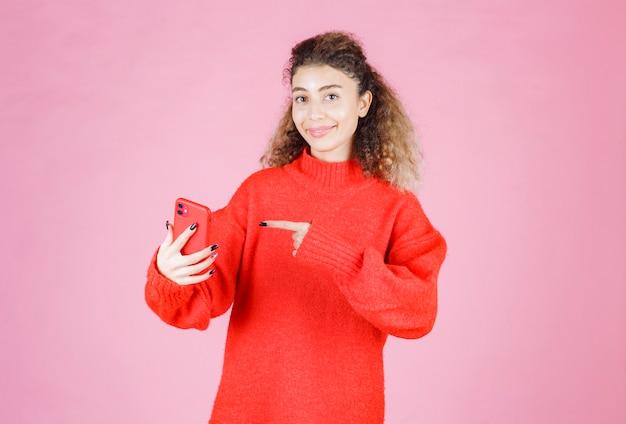 Donna che tiene e indica il suo nuovo smartphone di marca.