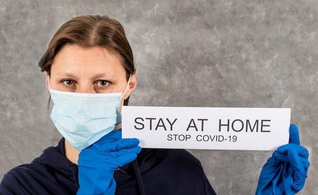 コロナウイルスの蔓延に対抗するためのマッサージ「家にいる」とポスターを保持している女性