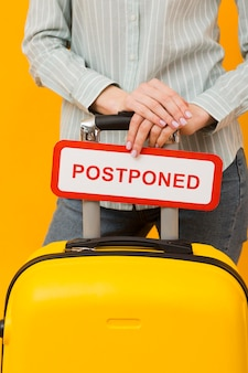 Woman holding a postponed card close-up