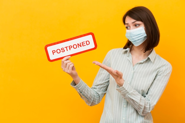 Woman holding a postponed sign on yellow background