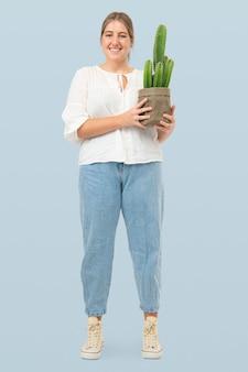 持続可能な包装で鉢植えのサボテンを保持している女性