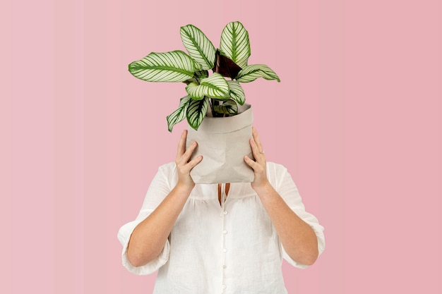 Woman holding potted plant in sustainable packaging