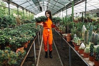 Woman holding potted plants in greenhouse
