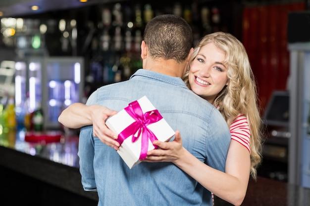 Женщина держит подарок во время обнимать парня