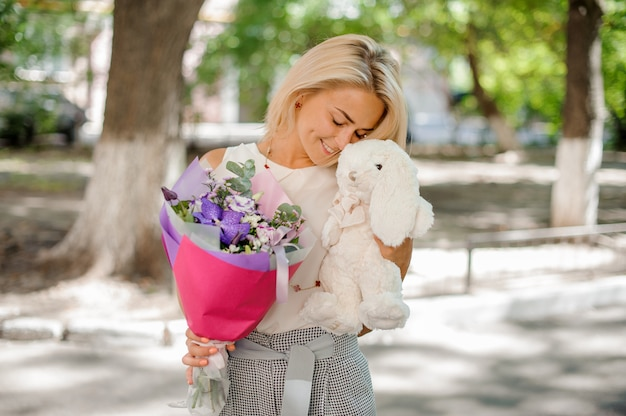 Woman holding a pretty composition of flowers and toy