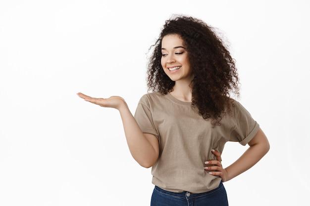 開いた手で製品を保持し、笑顔の幸せそうな顔で手のひらを見て、白の上に立っている女性