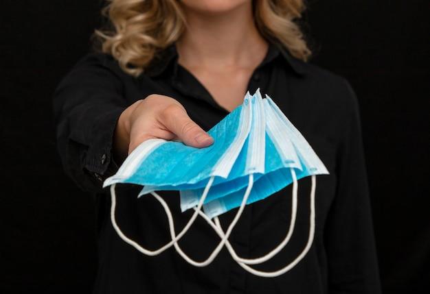 Женщина, держащая защитные маски для лица