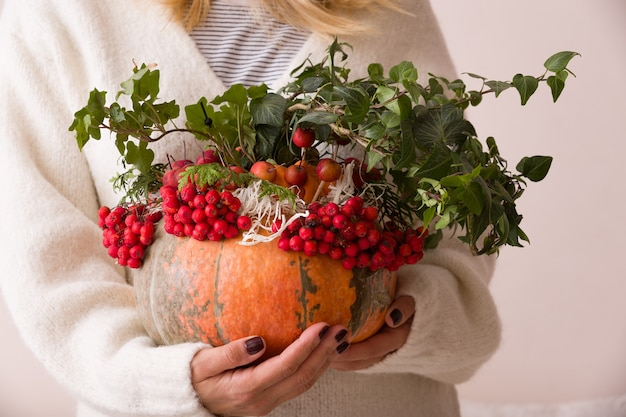 Женщина держит тыкву, украшенную для сервировки стола и празднования дня благодарения хэллоуина