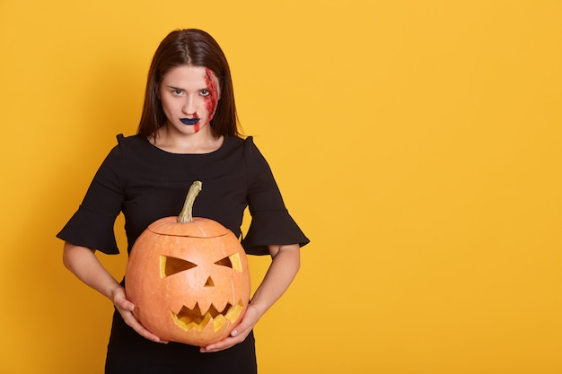 Woman holding pumpkin in studio isolated over yellow