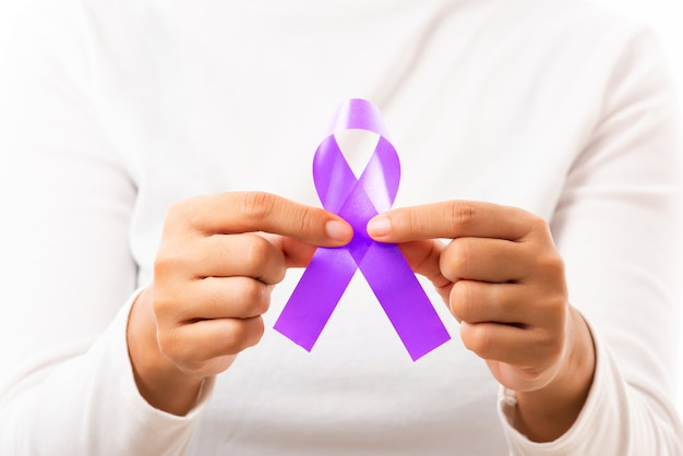 Woman holding purple ribbon on hand symbol of pancreatic cancer