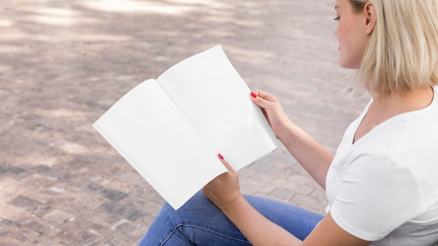 Woman holding and reading book outdoors