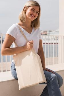Женщина, держащая перерабатываемый мешок и смеется