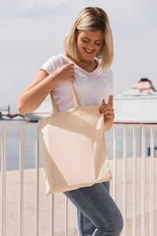 リサイクル可能なバッグを保持し、フェンスに寄りかかって女性