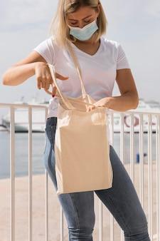 Женщина, держащая перерабатываемый мешок и носящая медицинскую маску