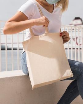 Женщина держит перерабатываемый мешок и носит защитную маску