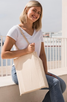 Woman holding recyclable bag and laughs