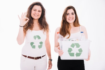 Woman holding recycle bin filled with trash and her friend showing ok sign