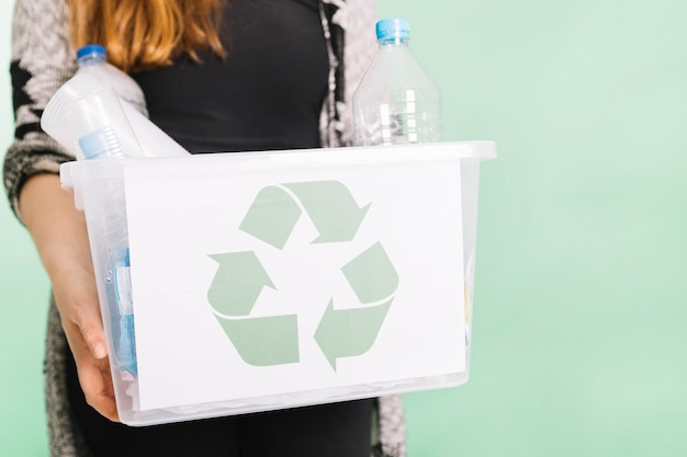Woman holding recycle crate for recycling against pastel background