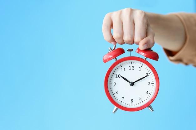 青い背景のクローズアップで彼女の手に赤い目覚まし時計を保持している女性