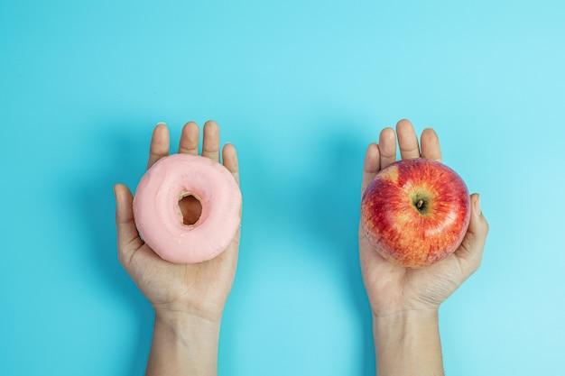 빨간 사과와 분홍색 도넛을 들고 있는 여성, 과일 중에서 선택하는 여성은 건강한 음식이고 달콤한 음식은 건강에 해로운 정크 푸드입니다. 다이어트, 비만, 식습관 및 영양 개념