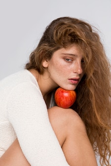 Woman holding a red apple between her face and knee