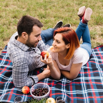 Woman holding red apple in hand lying with her boyfriend on blanket