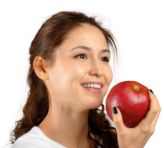 Женщина держит красное яблоко