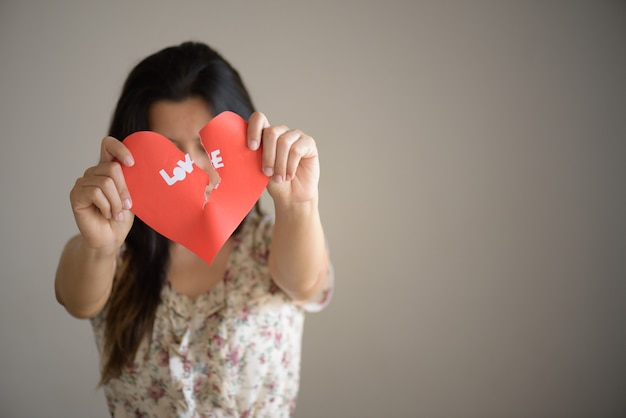 Woman holding red broken heart with love text. valentines day concept