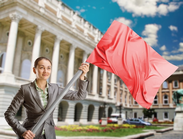Woman holding a red flag stands against building