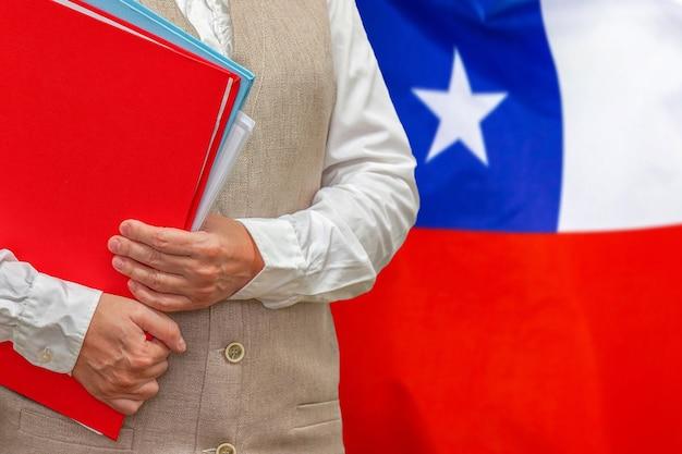 後ろにチリの旗と赤いフォルダーを保持している女性