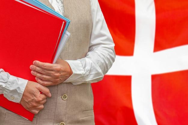 後ろにデンマークの旗と赤いフォルダーを保持している女性