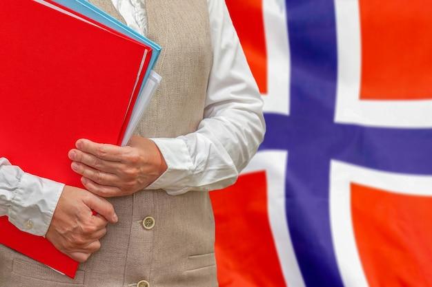 後ろにノルウェーの旗と赤いフォルダーを保持している女性