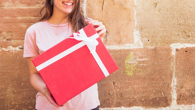 Woman holding red gift box against weathered wall